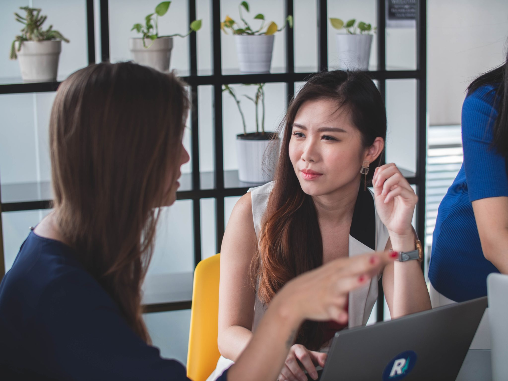 two women talking in front of laptop computer