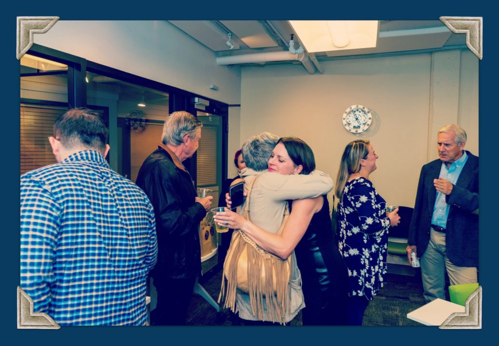 two people hugging in a room full of people