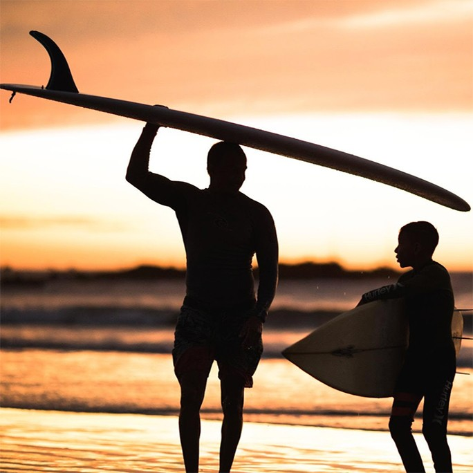 father and son holding surf boards at sunset