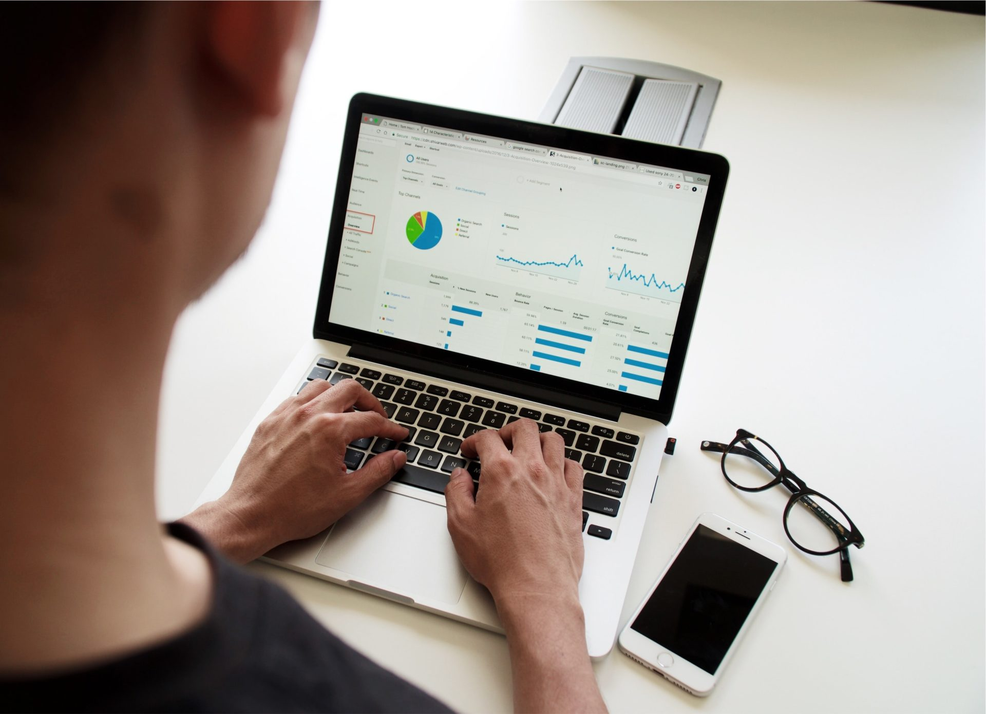 man typing on computer with graphs on screen